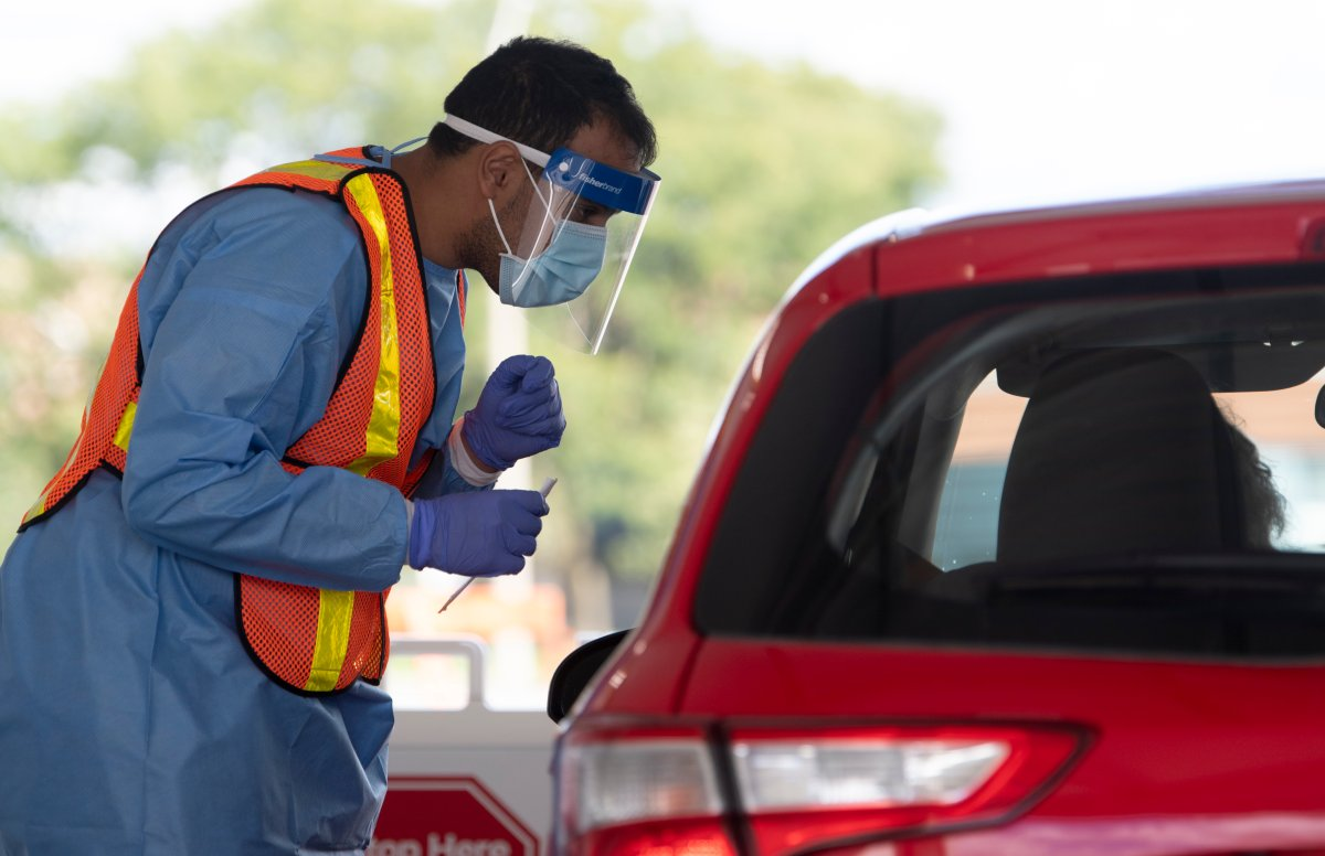 Ottawa health personnel speak with a driver before administering a COVID-19 test at a drive-thru test centre in Ottawa, Friday, Sept. 4, 2020.