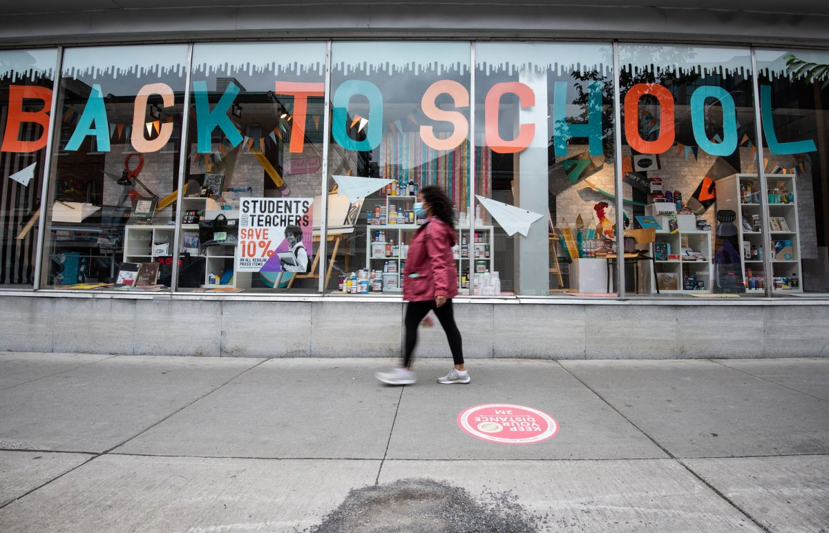 A person walks past a storefront advertising a back-to-school sale in Ottawa on the Labour Day Long Weekend, Monday, Sept. 7, 2020, in the midst of the COVID-19 pandemic.