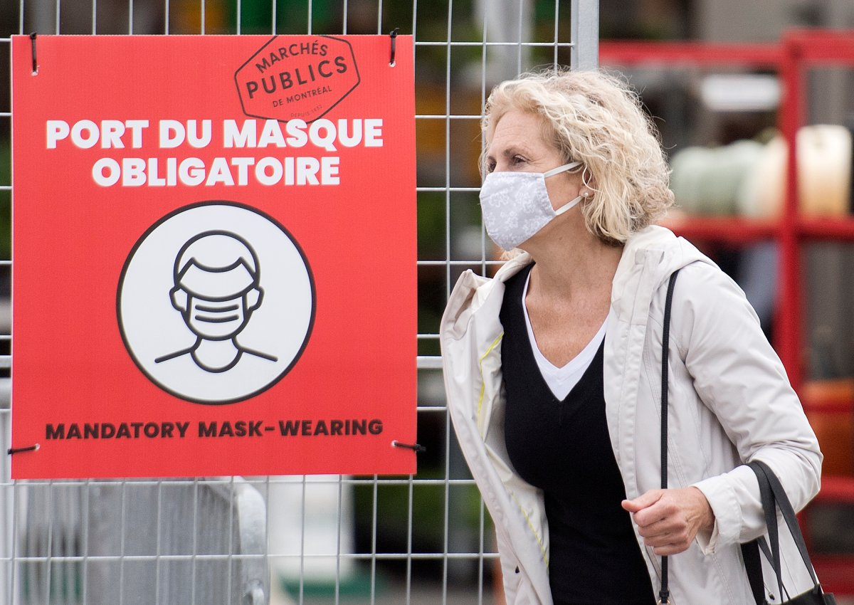 A woman wears a face mask as she walks by a sign instructing people to wear masks at a market in Montreal, Sunday, Sept. 13, 2020, as the COVID-19 pandemic continues in Canada and around the world.