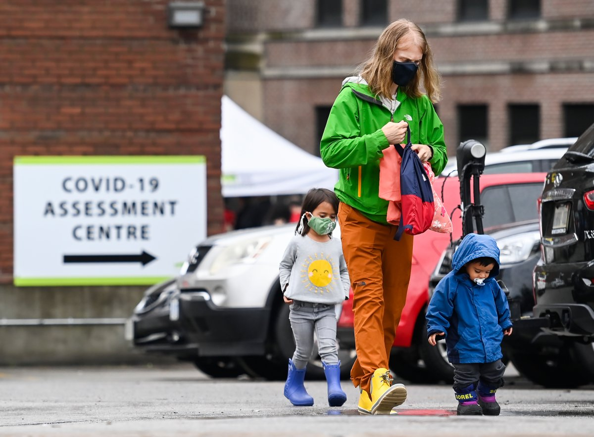 A family walks to line up to be tested for COVID-19 at a testing centre in Toronto on Sunday, Sept. 13, 2020.