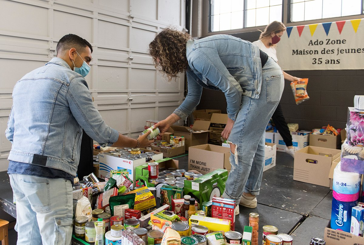 Volunteers sort through donated food items and other sundries during the 'September 13th Miracle' food drive in Montreal, Sunday, Sept. 13, 2020.