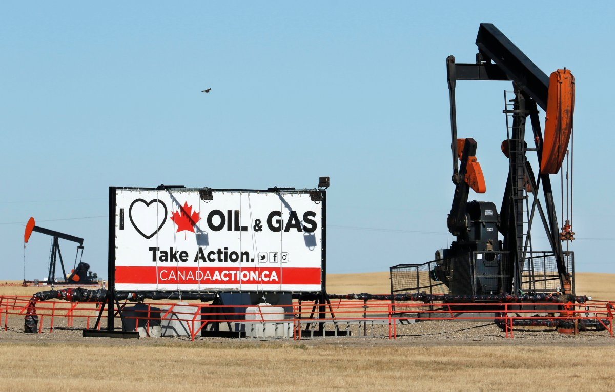 A sign supporting the oil and gas industry beside two oilfield pumpjacks pumping crude along the Trans-Canada Highway near Brooks, Alta., on Sept. 11, 2020.