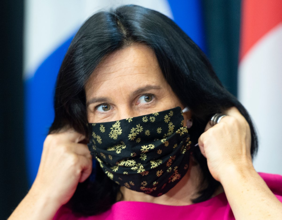 Montreal Mayor Valérie Plante removes her face mask as she arrives at a news conference, Friday, Sept. 18, 2020  in Montreal.
