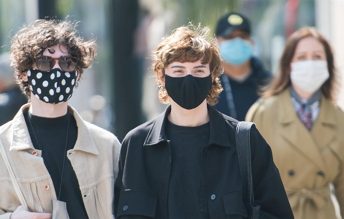 People wear face masks as they wait to cross a street in Montreal, Monday, September 21, 2020, as the COVID-19 pandemic continues in Canada and around the world.