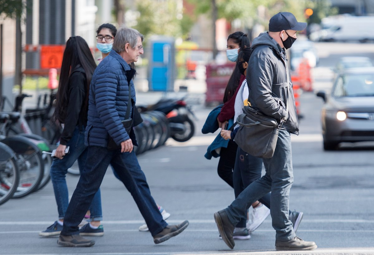 Some wear face masks as they walk along a street in Montreal, Monday, September 21, 2020, as the COVID-19 pandemic continues in Canada and around the world.