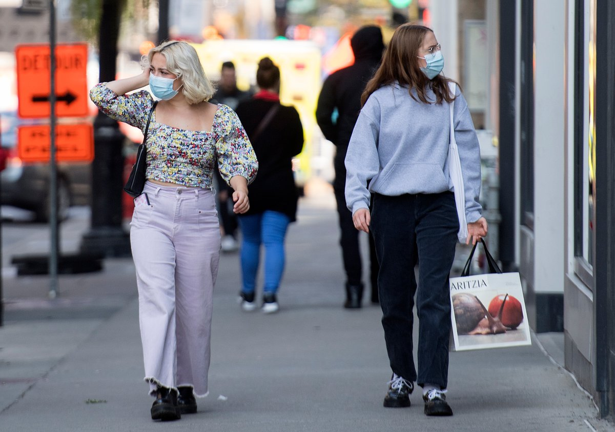 People wear face masks as they walk along a street in Montreal, Monday, September 21, 2020, as the COVID-19 pandemic continues in Canada and around the world.