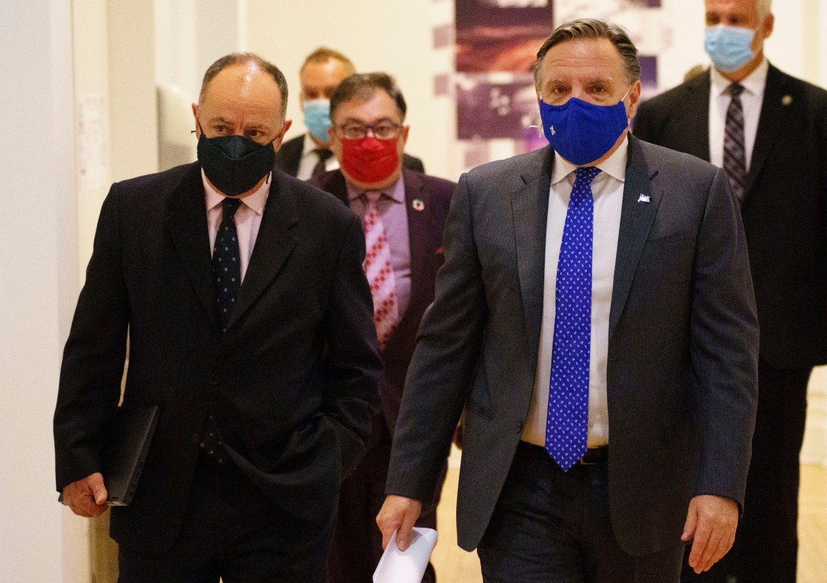 Quebec Premier Francois Legault arrives at a news conference flanked by Health Minister Christian Dube, left and Dr. Horacio Arruda, Quebec's director of public health, in Montreal, on Monday, September 28, 2020.