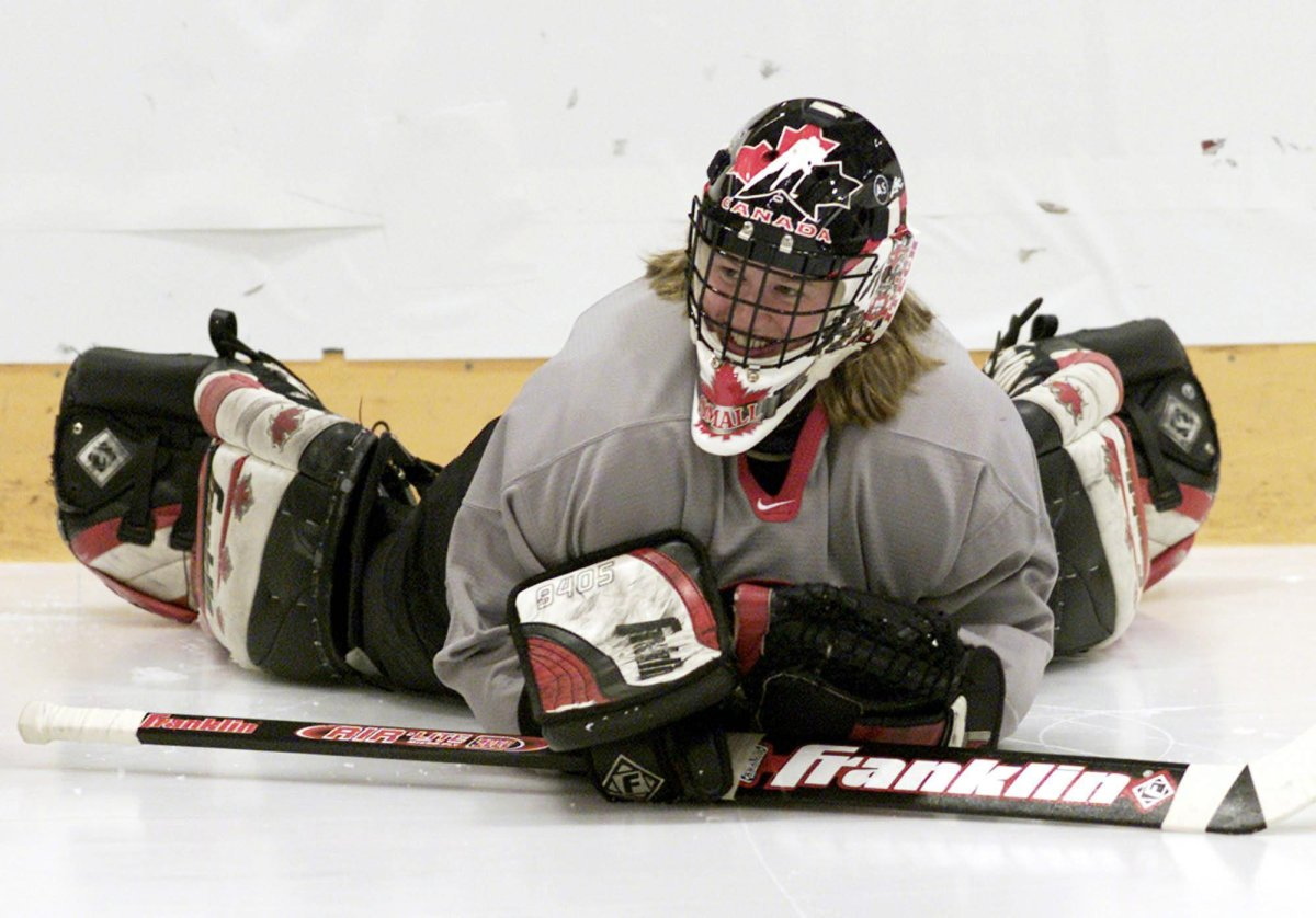 Canadian Women's hockey team goalie Sami Jo Small smiles as she lies on the ice before practice in Calgary, Wednesday March 26, 2003.
