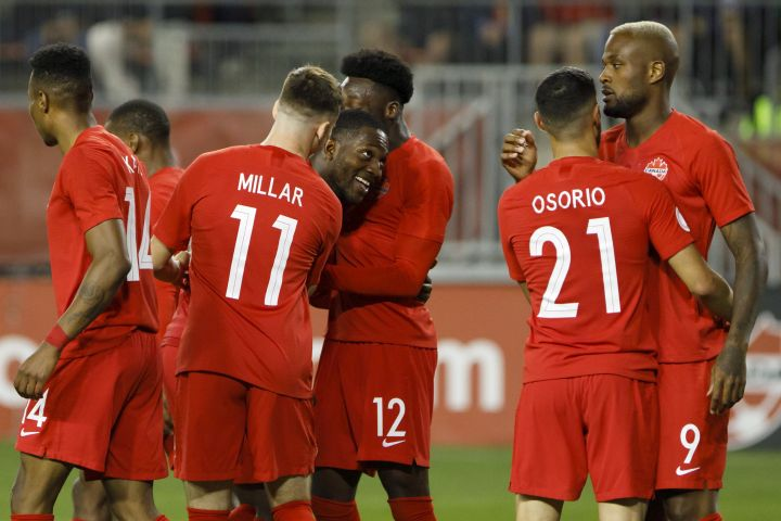 Canada defender Doneil Henry, centre left, celebrates with teammates midfielder Liam Millar (11) and midfielder Alphonso Davies (12) as he celebrates a goal during second half of CONCACAF Nations League play in Toronto on September 7, 2019.