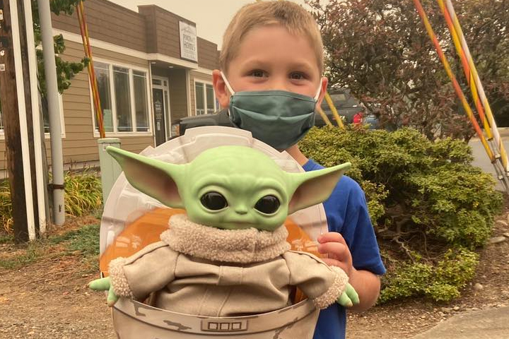 Carver Tinning, 5, is shown with the Baby Yoda toy he donated to firefighters in Oregon.