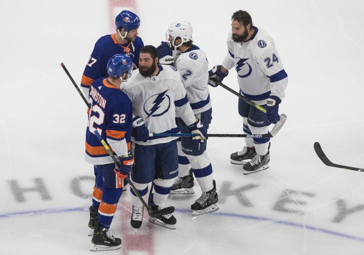 Tampa Bay Lightning's Pat Maroon (14), Luke Schenn (2) and Zach Bogosian (24) have words with New York Islanders' Ross Johnston (32) and Matt Martin (17) during warm up before NHL Eastern Conference final playoff action in Edmonton on Sunday, Sept. 13, 2020.