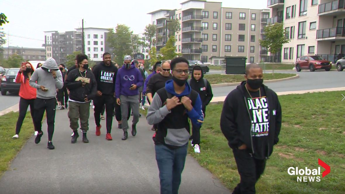 Dozens gathered outside Charles P. Allen High School to walk 16-year-old Demario Chambers to school on Tuesday, Sept. 8, 2020.