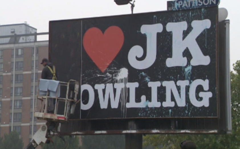Crews remove a billboard declaring love for author JK Rowling in Vancouver, after it was defaced on Saturday, Sept. 12, 2020.
