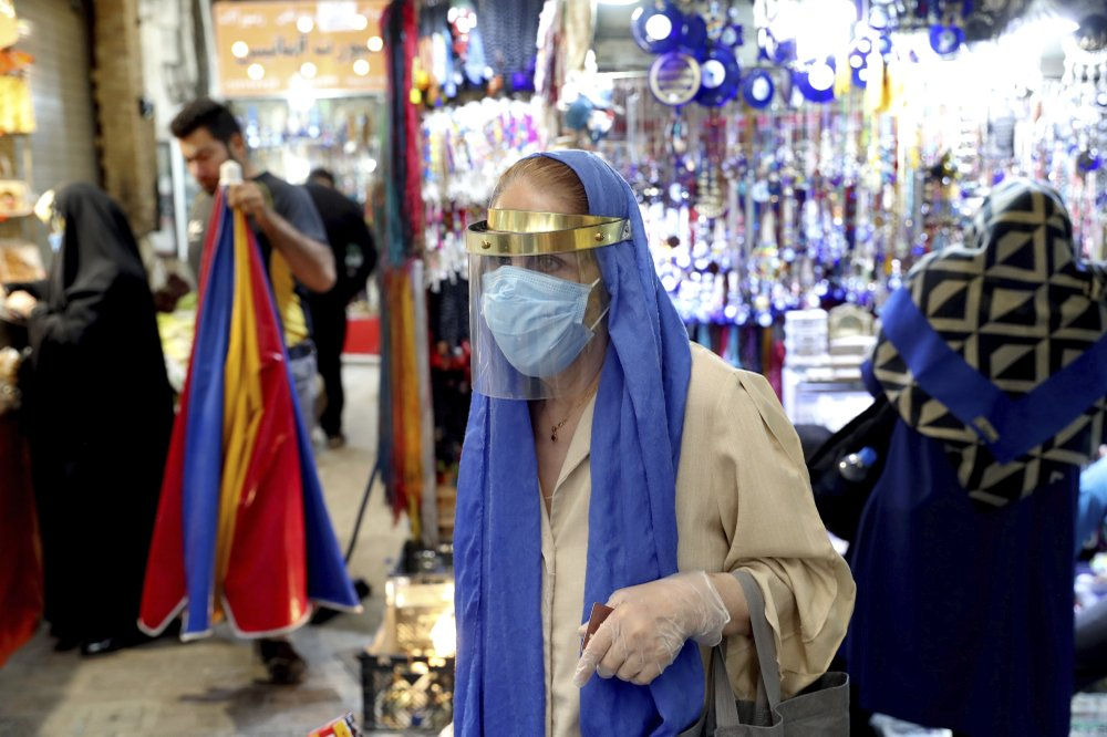 A woman wearing a protective face mask and gloves to help prevent the spread of the coronavirus walks through the Tajrish traditional bazaar in northern Tehran, Iran, Thursday, Oct. 15, 2020. Eight months after the pandemic first stormed Iran, pummeling its already weakened economy and sickening officials at the highest levels of its government, authorities appear just as helpless to prevent its spread.