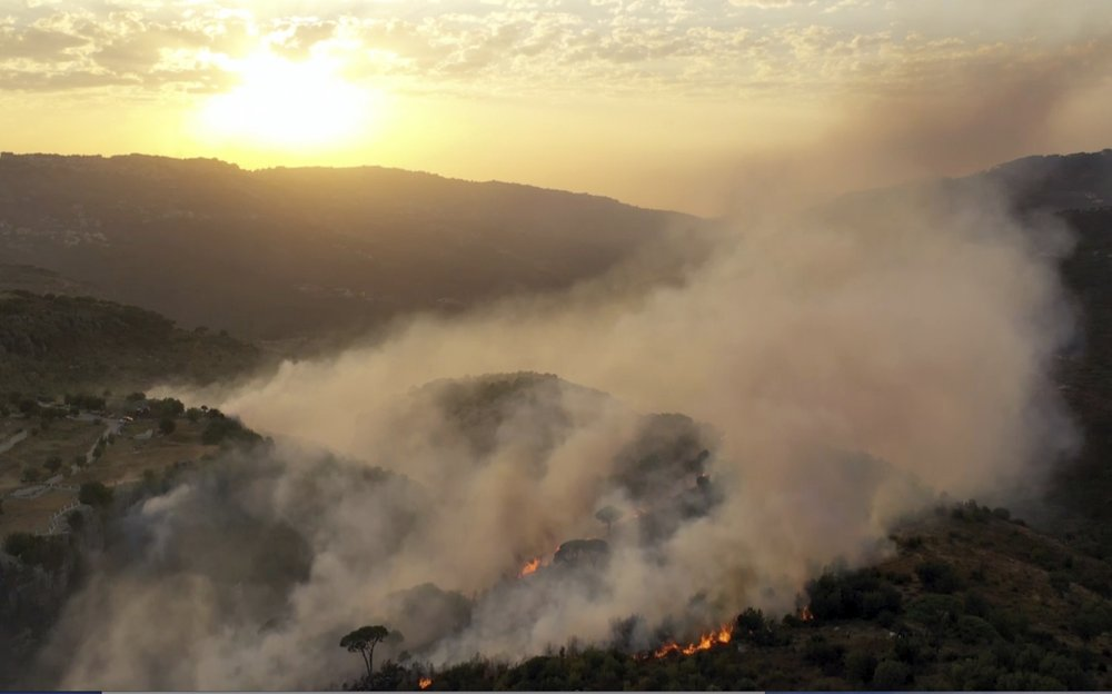 In this frame grab from video, flames rise at the scene of forest fire in Ras el-Harf village, in the Baabda district, Lebanon, Friday, Oct. 9, 2020. Wildfires around the Middle East triggered by a heatwave hitting the region have killed two people, forced thousands of people to leave their homes and detonated landmines along the Lebanon-Israel border, state media and officials said Saturday.