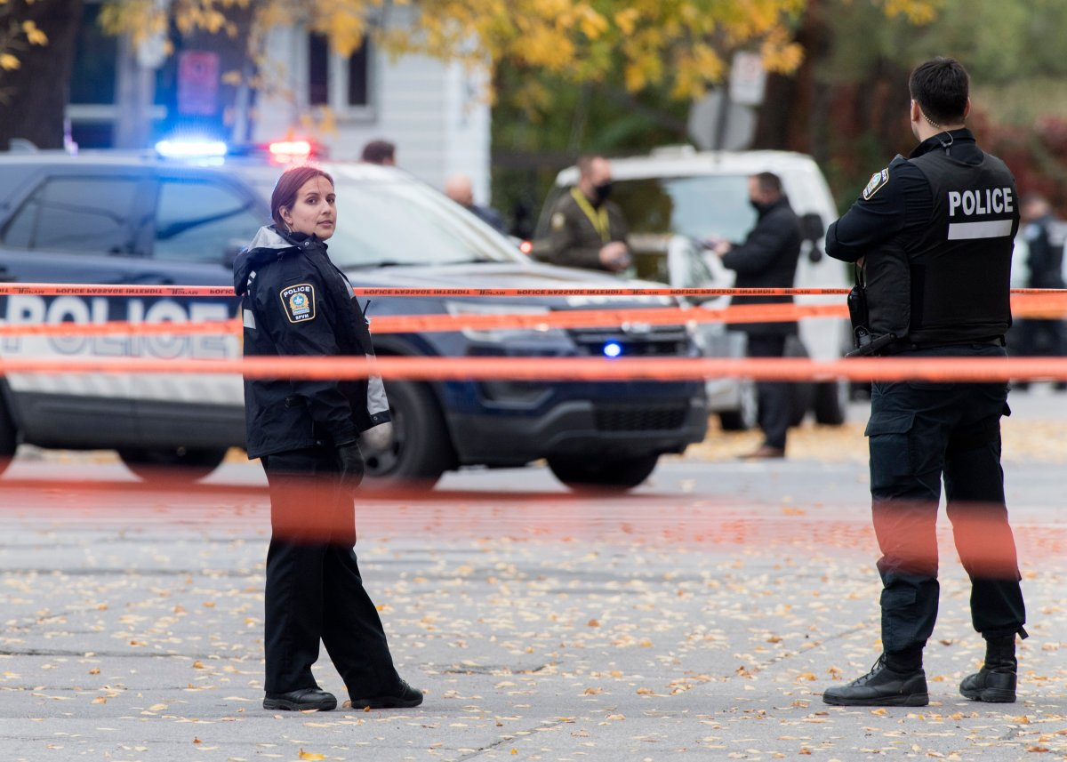 Police are shown at the scene of a shooting in Montreal, Saturday, October 2, 2020. Quebec's police watchdog says two women are dead and one man injured after a shooting in Montreal. The Independent Investigations Bureau (BEI) says a man shot and killed two women Saturday afternoon.