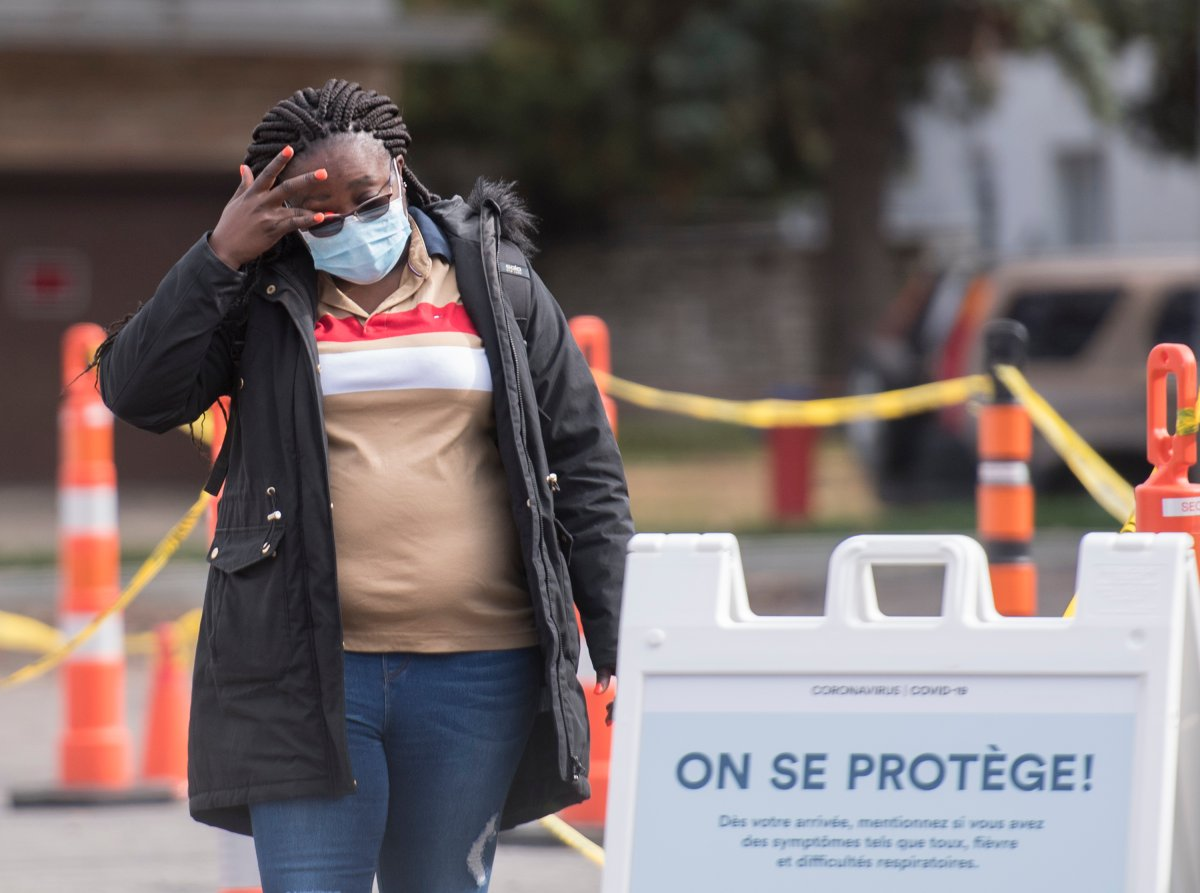 A woman waits to be tested for COVID-19 at a testing clinic in Montreal, Sunday, October 4, 2020, as the COVID-19 pandemic continues in Canada and around the world.