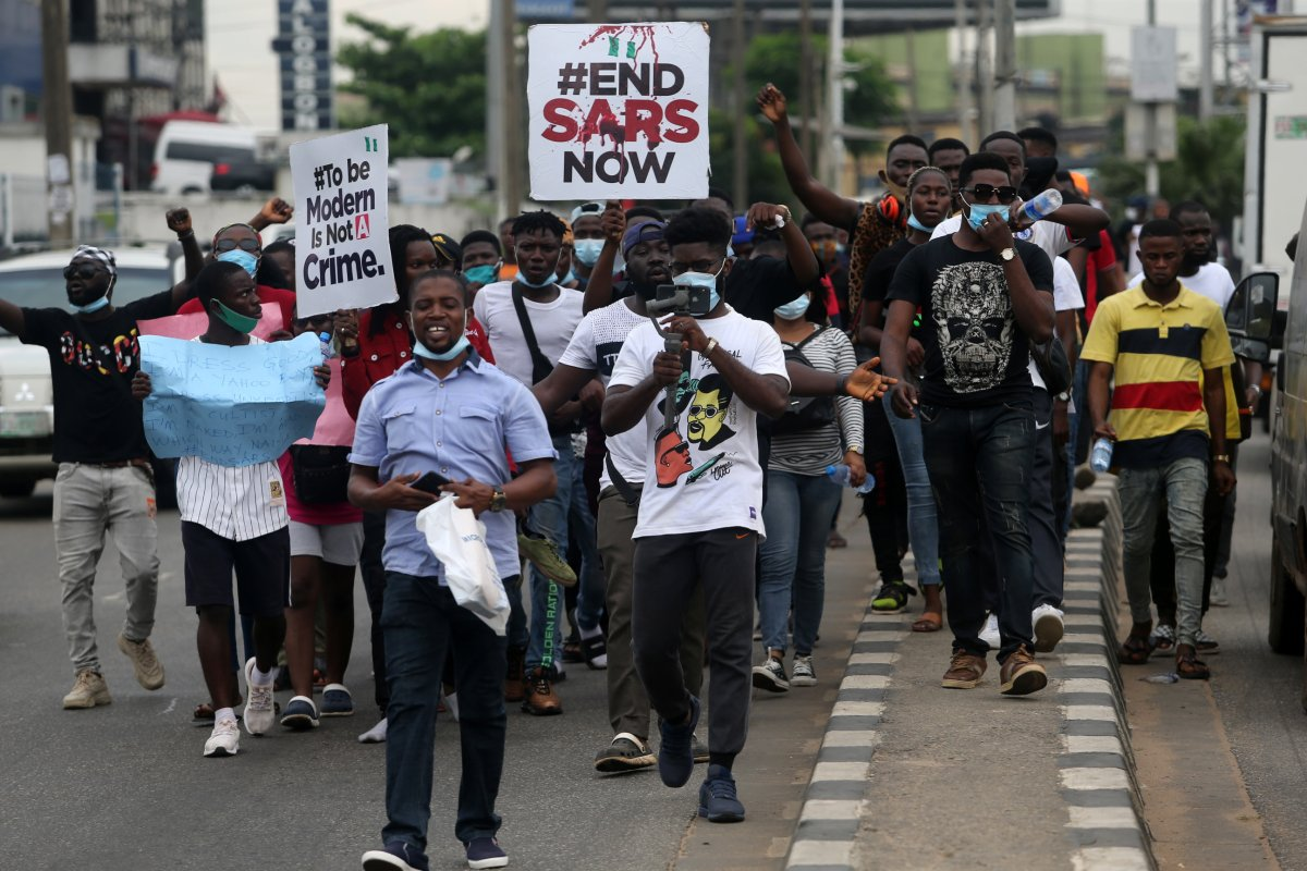 Protesters hold banners as they walk along a road during a protest against the Nigeria rogue police, otherwise know as Special Anti-Robbery Squad (SARS), in Ikeja district of Lagos, Nigeria, Oct. 9, 2020.