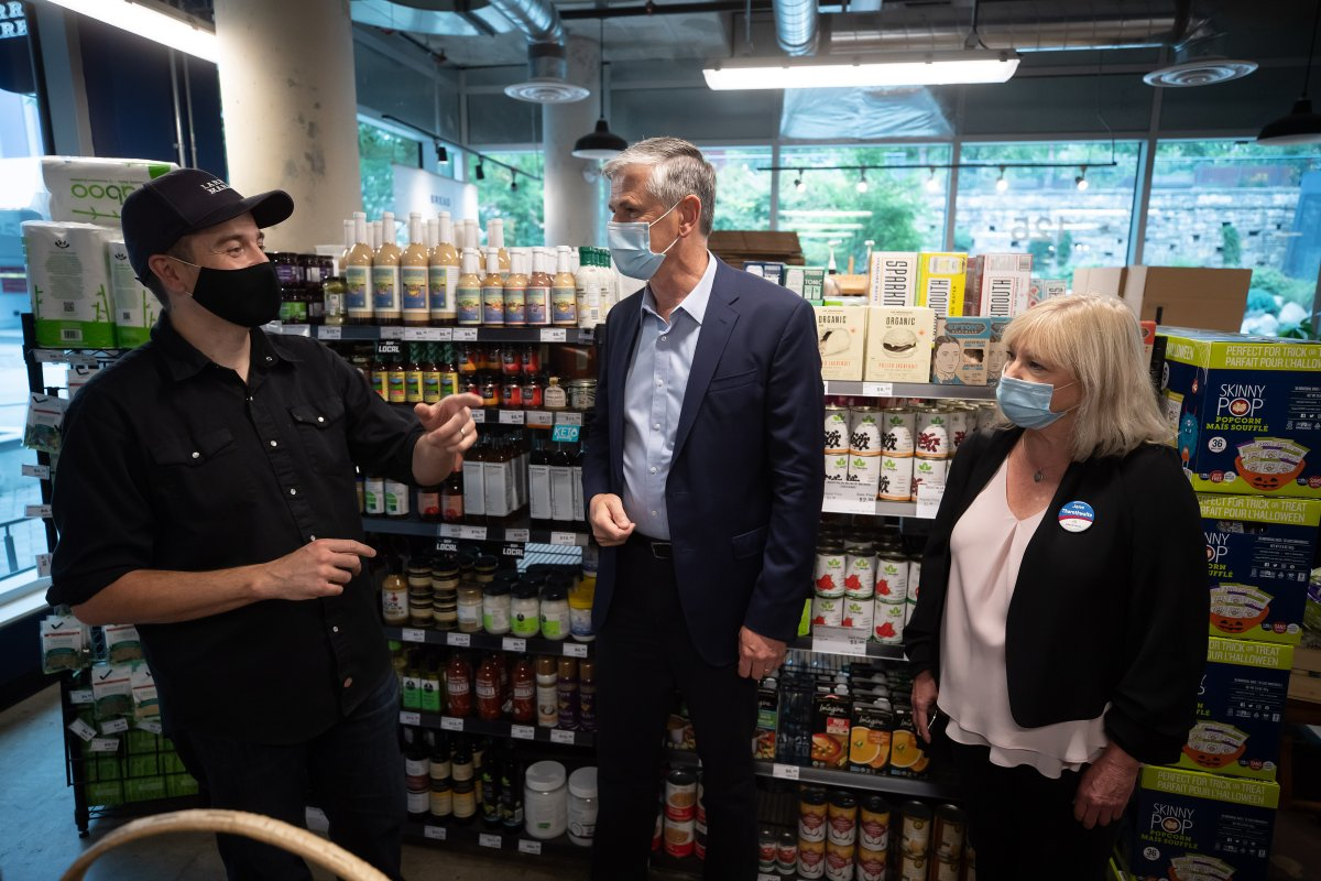 Liberal Leader Andrew Wilkinson, centre, and local candidate Jane Thornthwaite, right, listen to Larry's Market owner Ryan Dennis during a campaign stop at the grocery store, in North Vancouver, on Sunday, October 4, 2020. A provincial election will be held in British Columbia on October 24.