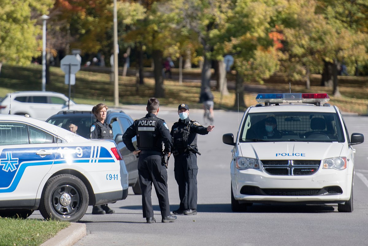 Police officers talk as the block the entrance to a parking lot in Mount Royal Park in Montreal, Monday, October 12, 2020, as the COVID-19 pandemic continues in Canada and around the world.