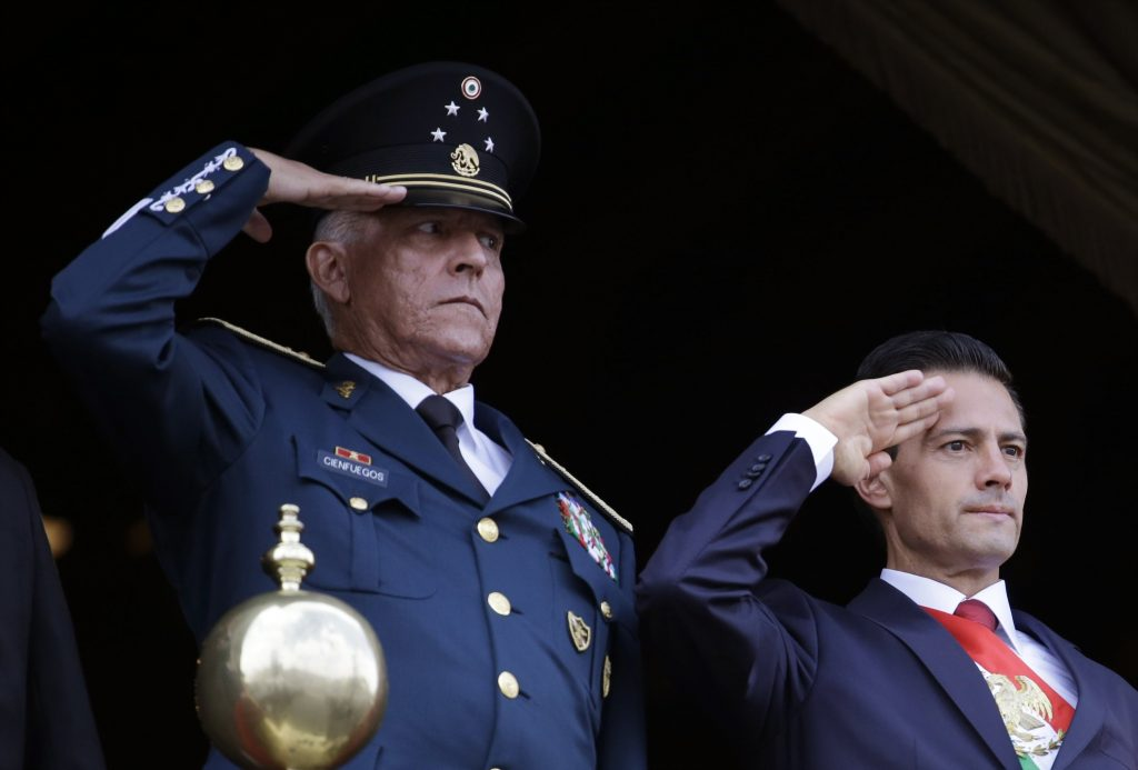 FILE - In this Sept. 16, 2016 file photo, Defense Secretary Gen. Salvador Cienfuegos, left, and Mexico's President Enrique Pena Nieto, salute during the annual Independence Day military parade in Mexico City's main square. Mexico's top diplomat says the country's former defense secretary, Gen. Salvador Cienfuegos, has been arrested in Los Angeles. Foreign Relations Secretary Marcelo Ebrard wrote Thursday, Oct. 15, 2020 in his Twitter account that U.S. Ambassador Christopher Landau had informed him of Cienfuegos' arrest.
