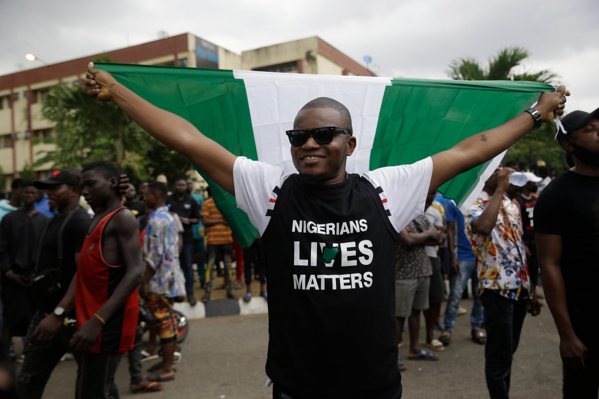 A man holds a Nigerian flag as he demonstrates on the street to protest against police brutality in Lagos, Nigeria, Oct. 16, 2020.