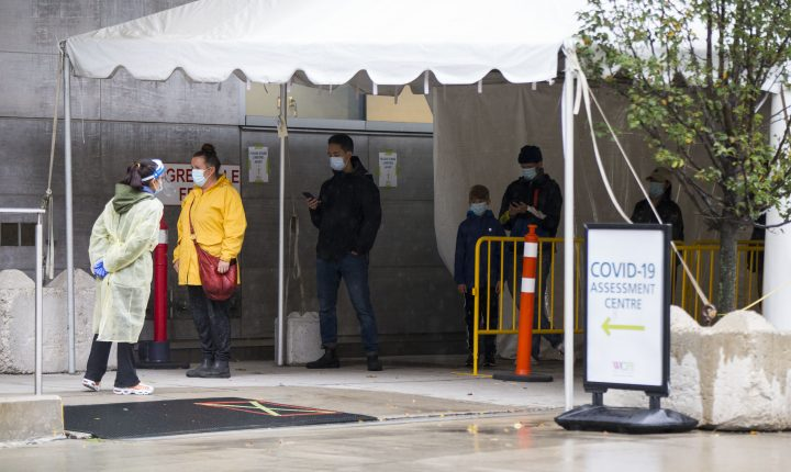 People line up for COVID-19 testing outside a COVID-19 assessment centre in Toronto on Oct. 15, 2020.