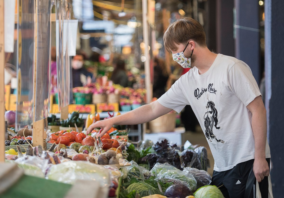 A man wears a face mask as he shops at a market in Montreal, Sunday, Oct. 18, 2020, as the COVID-19 pandemic continues in Canada and around the world.