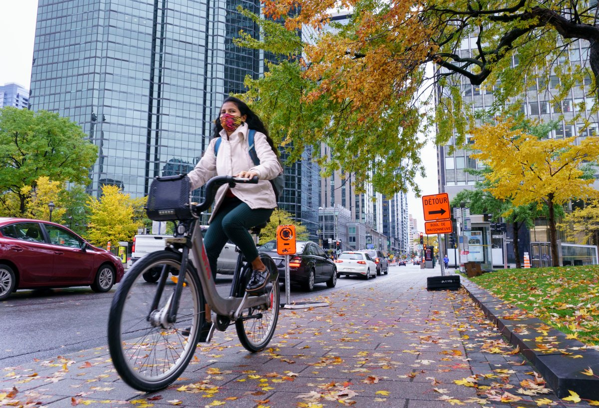 A woman rides his bike in downtown Montreal, on Tuesday, October 20, 2020.