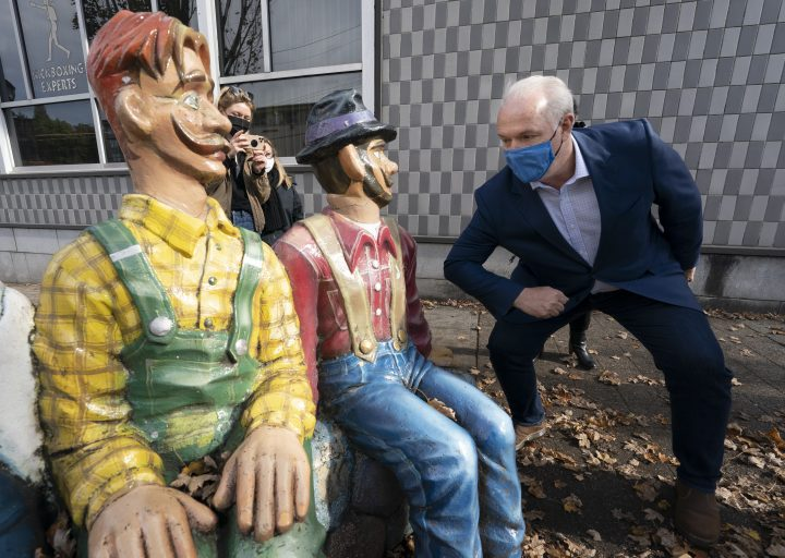 NDP Leader John Horgan pretends to elbow bump a statue as he main streets in Abbotsford, B.C., Wednesday, October 21, 2020.