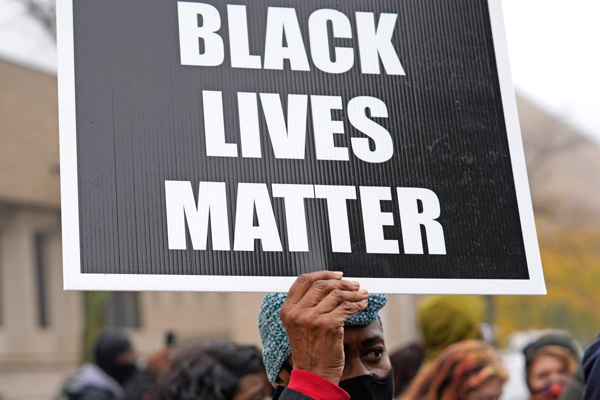A woman holds a sign during a protest rally for Marcellis Stinnette who was killed by Waukegan Police Tuesday in Waukegan, Ill., Oct. 22, 2020.