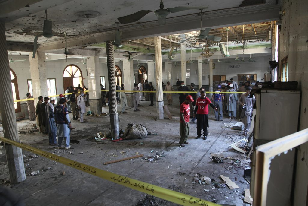 Rescue workers and police officers examine the site of a bomb explosion in an Islamic seminary in Peshawar, Pakistan, Tuesday, Oct. 27, 2020. A powerful bomb blast ripped through the Islamic seminary on the outskirts of the northwest Pakistani city of Peshawar on Tuesday morning, killing some students and wounding dozens others, police and a hospital spokesman said.