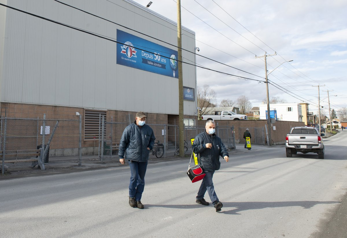 Workers walk outside the Olymel pork processing plant, Thursday, October 29, 2020 in Vallee-Jonction, Que. A COVID-19 outbreak at the plant southeast of Quebec City continues to grow.