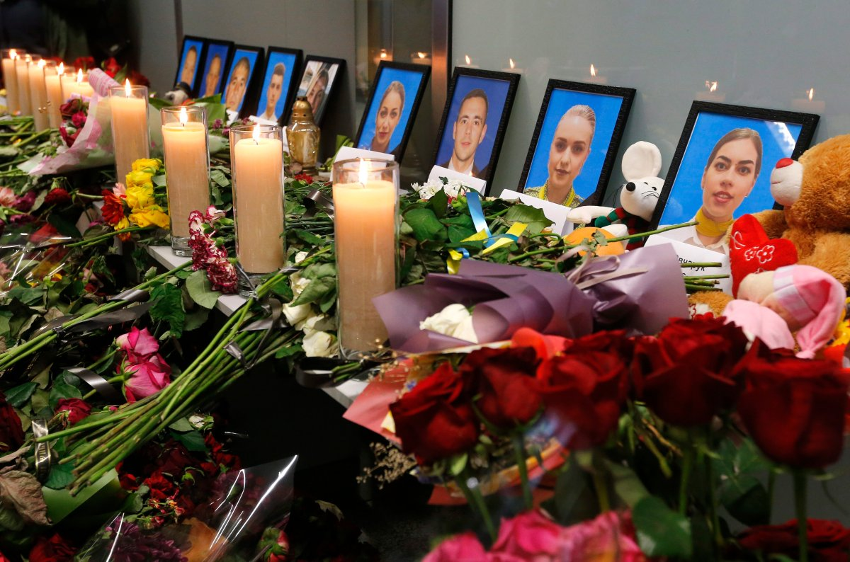 Flowers and candles are placed in front of portraits of the flight crew members of the Ukrainian 737-800 plane that crashed on the outskirts of Tehran, at a memorial inside Borispil international airport outside Kyiv, Ukraine, Saturday, Jan. 11, 2020.