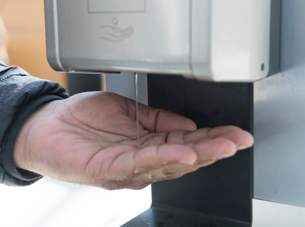 A man dispenses hand sanitizer in a shopping mall in the Montreal borough of Pointe-Claire, Saturday, March 14, 2020.