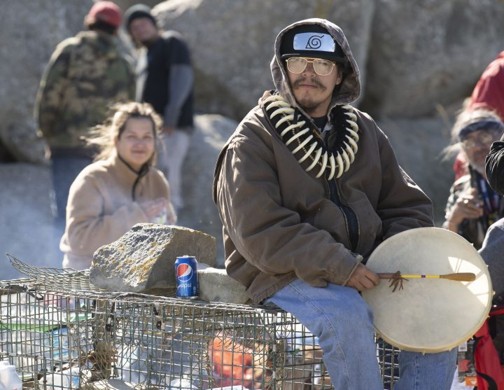 A Sipekne'katik First Nation community member holds a drum as he sits on lobster traps in Saulnierville, N.S. on Sunday, September 20, 2020.