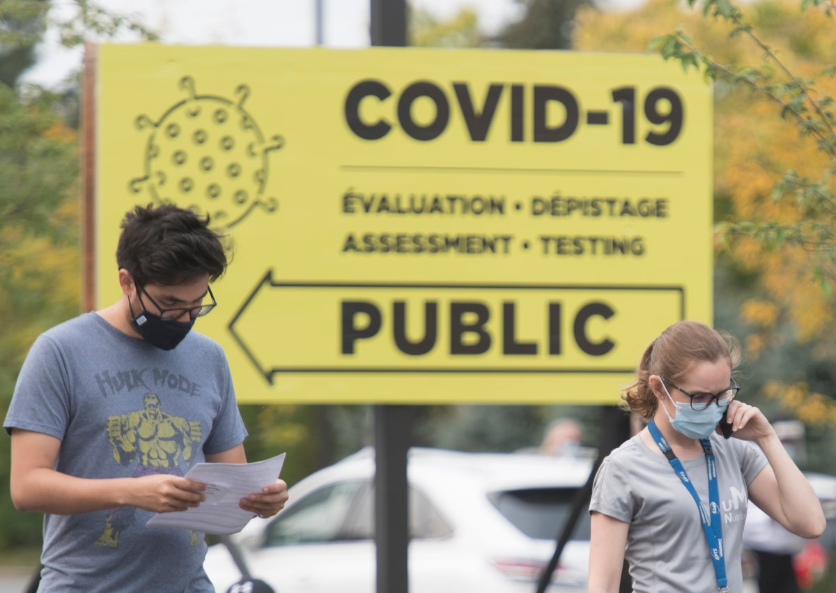 People wear face masks outside a COVID-19 testing clinic in Montreal, Sunday, Sept. 27, 2020, as the COVID-19 pandemic continues in Canada and around the world.