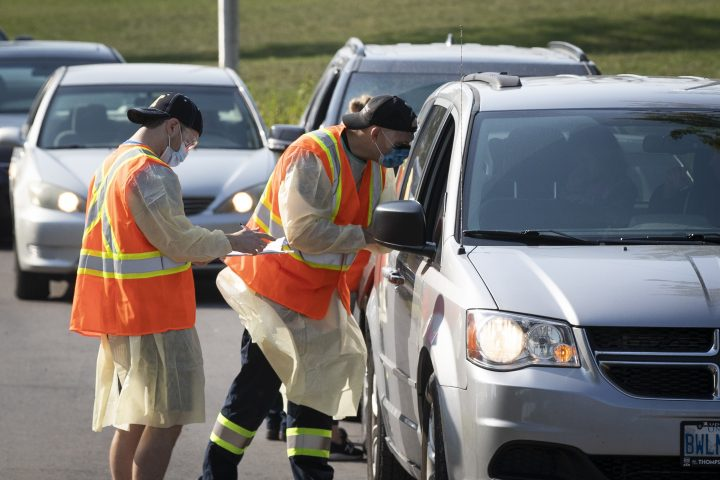 Staff tests people in their vehicle at the drive-thru Covid-19 assessment centre in Kingston, Ontario on Saturday, September 26, 2020.