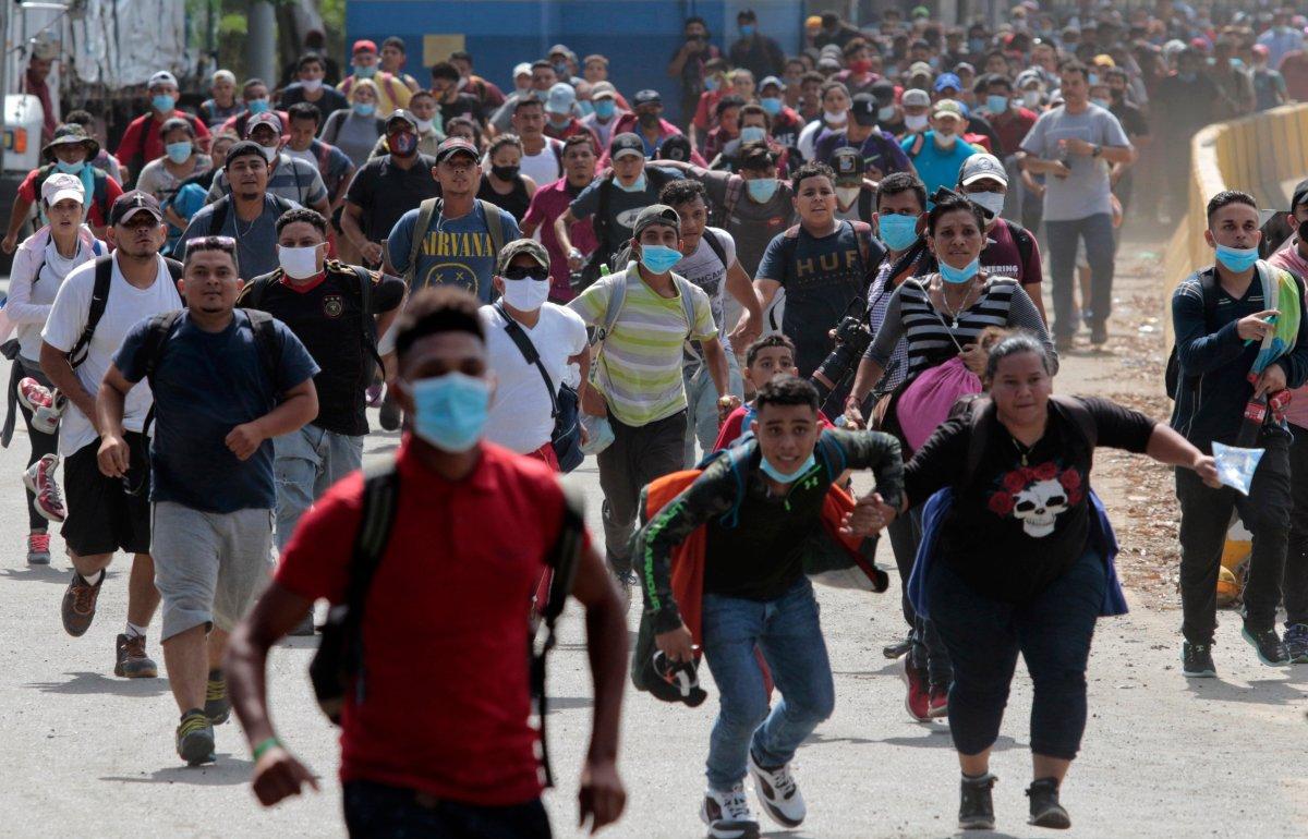 Migrants attempt to cross the border from Corinto, Honduras, into Corinto, Guatemala, Thursday, Oct. 1, 2020.