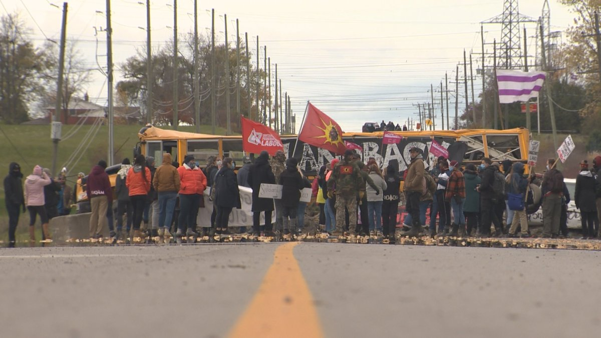"""Supporters marching to police barricades on Oct. 25, 2020 chanting """"land back"""", with Caledonia residents looking on."""