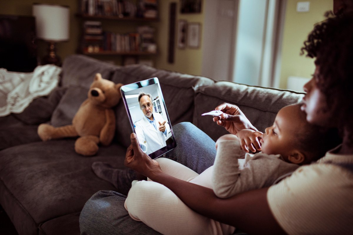 Close up of a mother and daughter consulting with their doctor over a video call on their digital tablet.