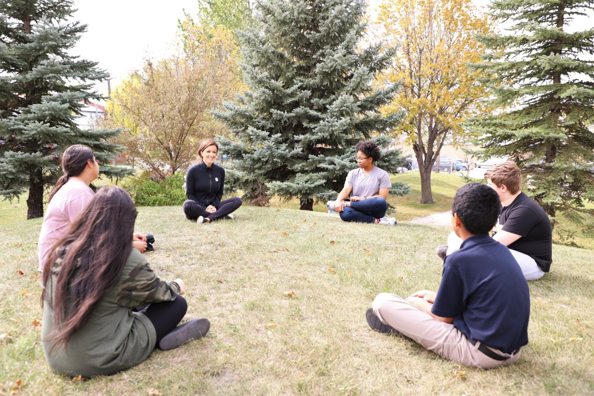 Project 11's Suzi Friesen, centre left, does socially distanced meditation work with students during COVID-19. The True North Youth Foundation program has increasingly turned to technology to continue its work through the pandemic.