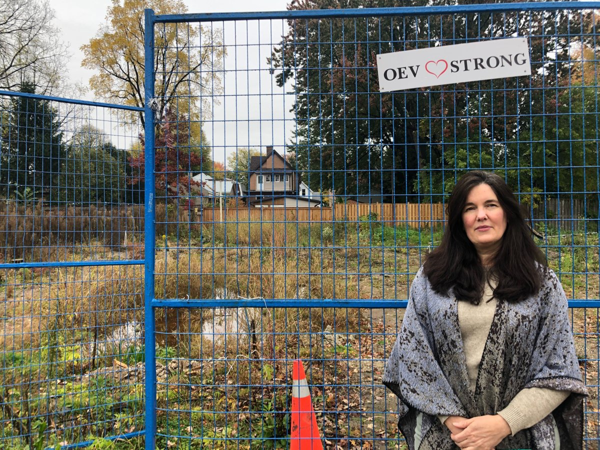 Karen Fisher stands in front of the empty lot where her Woodman Avenue home used to be. Last year's explosion in Old East Village saw the house completely destroyed.