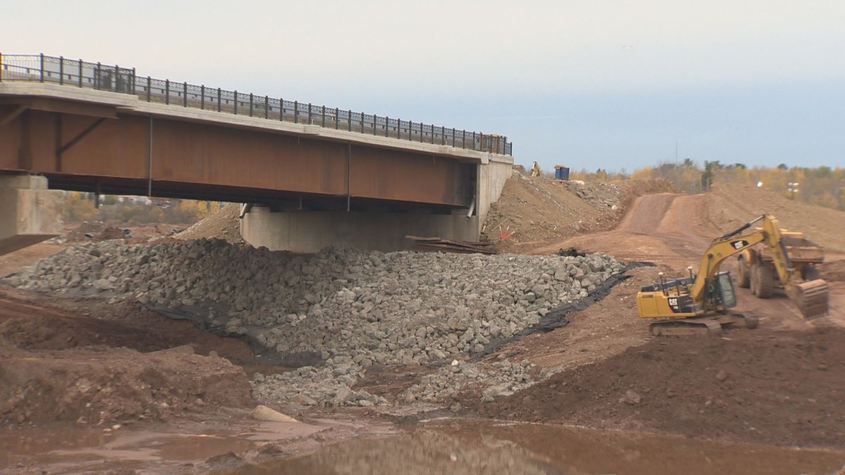 Workers continue to construct a bridge that was previously delayed. The bridge is now expected to open in November 2021.