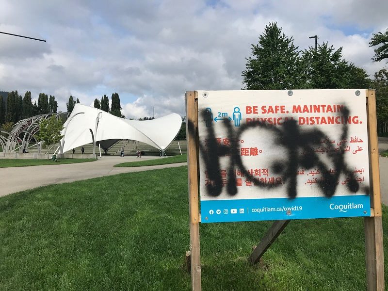 Police are searching for a suspect who allegedly vandalized signs in a Coquitlam park.
