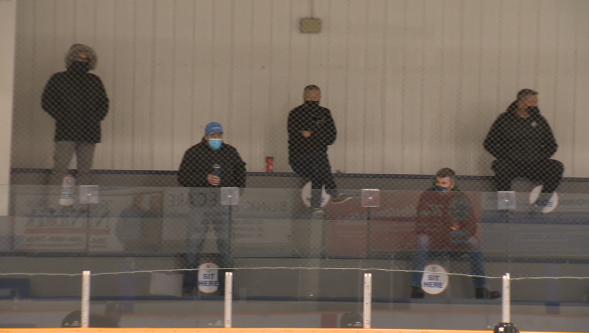 Parents spaced out watching a hockey practice at Southdale arena in Winnipeg on Oct. 25, 2020.