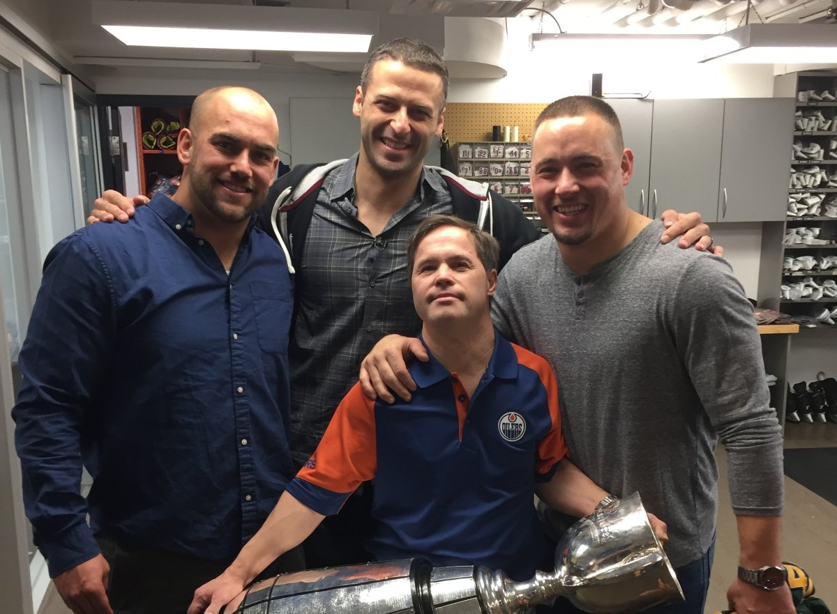 Joey Moss holds the Grey Cup with then EE Football Team members Ryan King (L), Mike Reilly (C) and J.C. Sherritt (R).