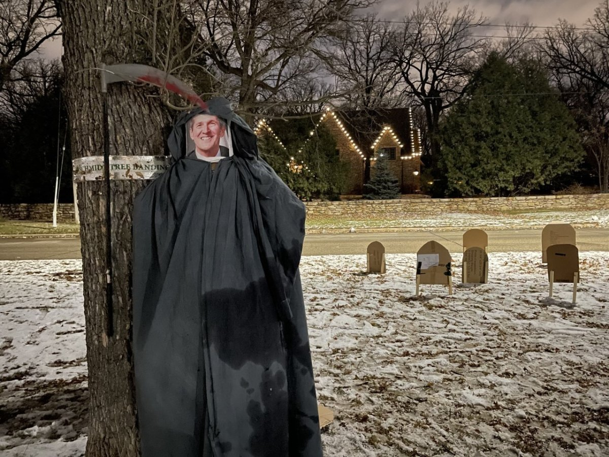 A photo of Manitoba Premier Brian Pallister is placed inside a Grim Reaper costume as part of a protest outside his Winnipeg home on Saturday, Oct. 31, 2020.