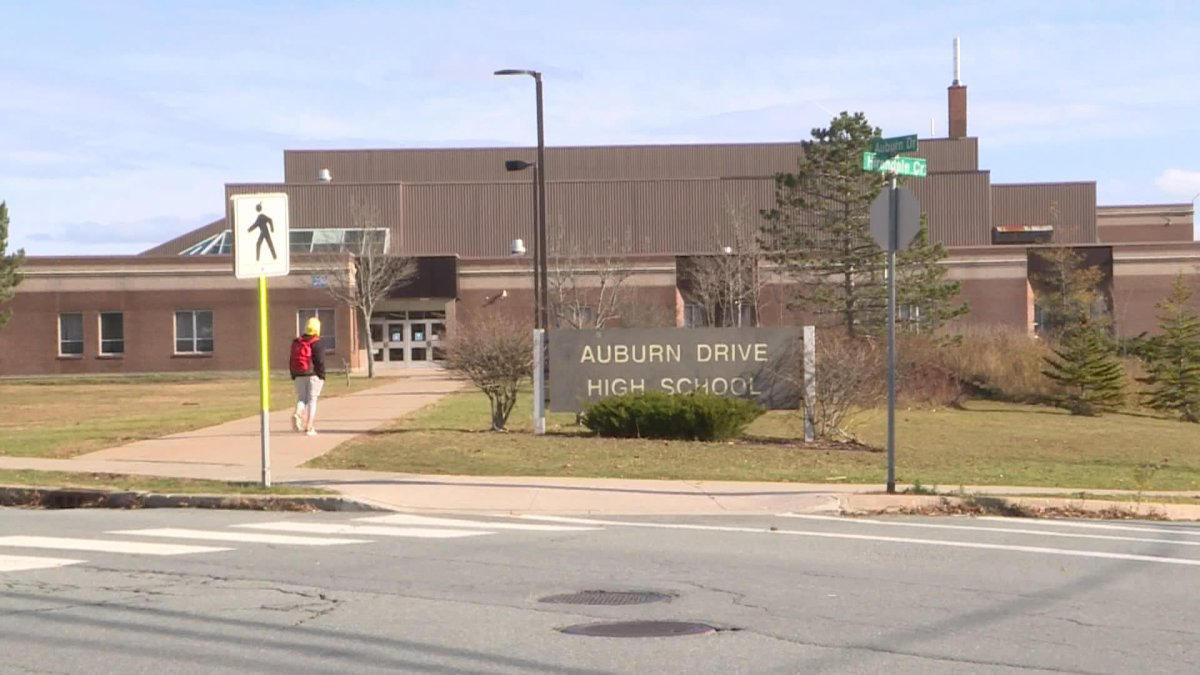 A student walks to Auburn Drive High School after a COVID case was confirmed at the school.
