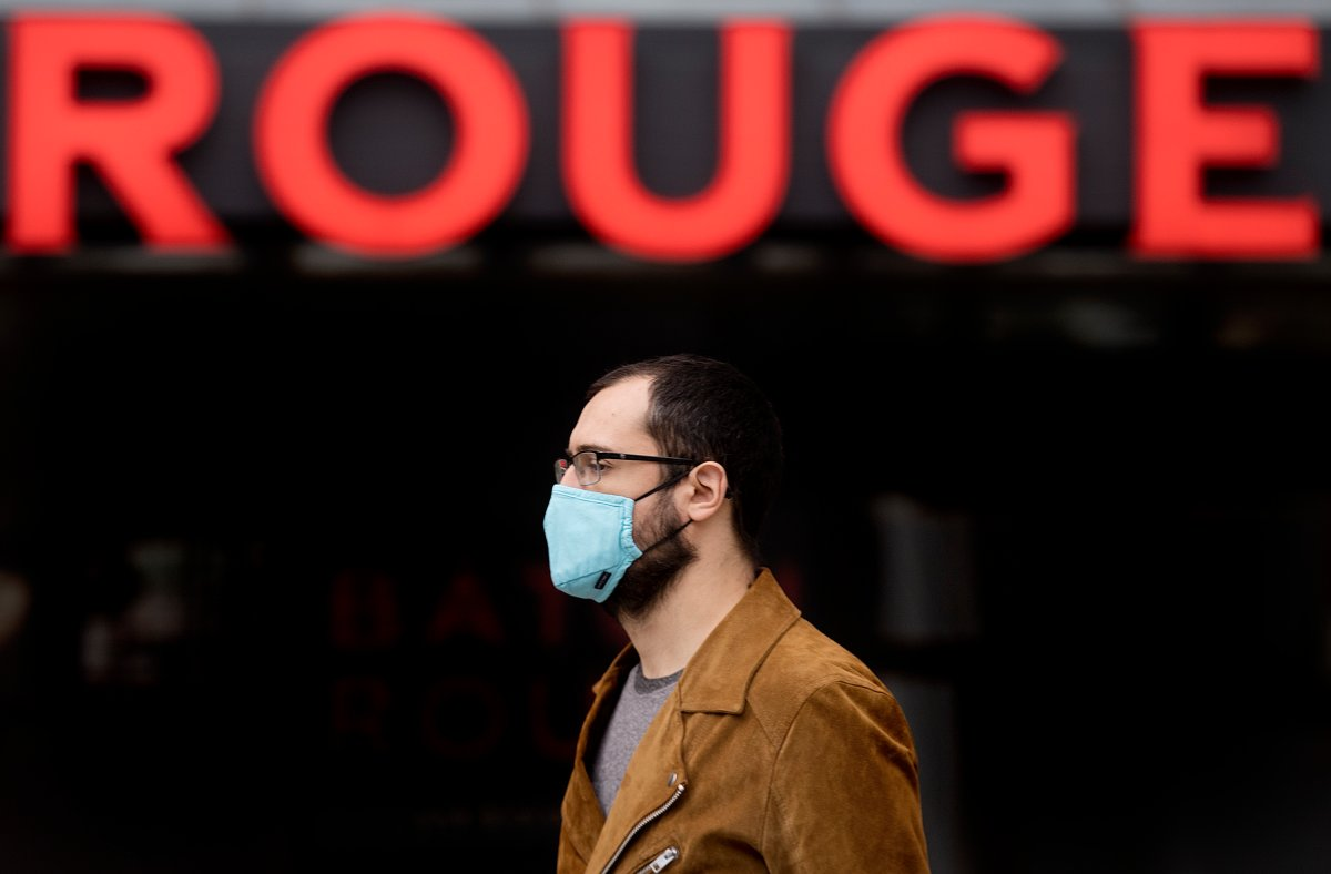 A man wears a face mask as he walks by the word Rouge in Montreal, Saturday, Oct. 10, 2020, as the COVID-19 pandemic continues in Canada and around the world.